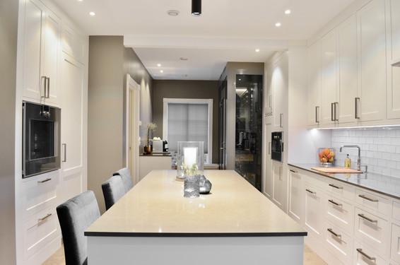 Slett profil på de hvitmalte frontene samt rette håndtak i børstet stål gir et passe stramt uttrykk på dette skreddersydde kjøkkenet