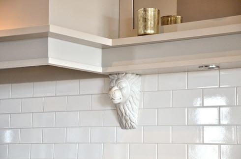 Detaljer fra kjøkkenhette med løvehode, spotter og dekorativ hylle