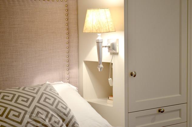 Nattbord innebygget i garderoben. Stofftrukket sengegavl. Malt i lys grå med dusty lilla tekstiler. Antikk tinn knotter