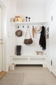 Praktisk og lett innredet entre med en kombinert sittebenk og radiatorskjuler med enkel hattehylle og knagger i antikk messing