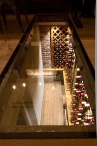 Glassplate i gulv på kjøkkenet gir gjennomsyn ned til vinrommet i kjelleren