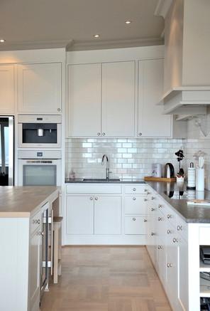 En side av kjøkkenet er skapene tilpasset takvinkelen og hver enkelt dør er vinklet mot takforingen. Farge på hette og vegg er Kalk, og klassisk hvit er brukt på innredningen generelt.