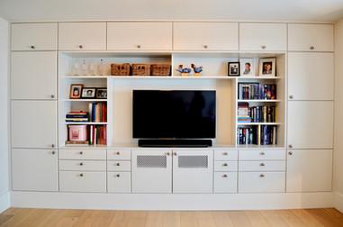 Plassbygget bokhylle i stue med praktiske skuffer og godt med skap til oppbevaring. Innebygget TV. Malte slette fronter i lys grå farge og antikk tinn knotter