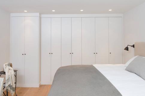 Gardrobeskap med slette fronter tilpasset på mål til vegg og tak. Legg merke til at deler av garderoben er laget grunnere for å gi mer plass i rommet