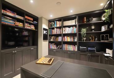 Åpne bokhyller og lukkede skap til spill, bøker og kontorutstyr, samt stor innebygget TV