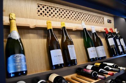 I den skråstilte vinhylla i eik er hedersplassen for de flotteste vinflaskene