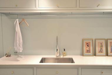 Lang fritthengende garderobestang under toppskap til å tørke hengende klær