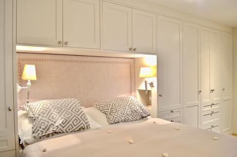 Skreddersydd seng innebygget i garderobeløsning. Stofftrukket sengegavl. nattbord innebygget i garderoben. Malt i lys grå med dusty lilla tekstiler