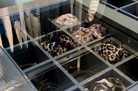 Skuffeinndelinger i garderobe øy til belter, skjerf og smykker med glassplate for praktisk gjennomsyn
