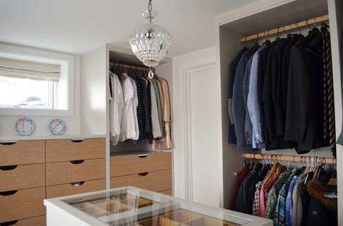 Spesialtilpasset Walk in closet med åpne garderobeskap til å henge klær og praktiske skuffeseksjoner i eik.  garderobe øy i midten