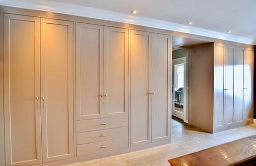 Skreddersydd garderobe i grå farge med enkel dørprofil tilpasset tak, vegger og døråpning gir et helhetlig og beskjedent uttrykk