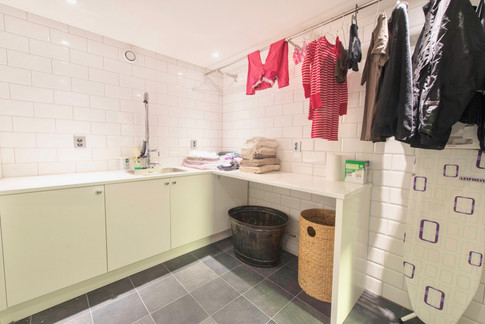 Praktisk innredet vaskerom. Godt med benkeplass og plass til skittentøysoppbevaring under benken. Lang kleshenger stang til å tørke klær. Armatur med høy dusj fra KWC