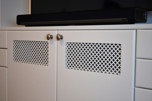 Detaljer fra bokhylle som viser TV benk med dekorerte plater til utlufting. Malte fronter i lys grå farge og antikk tinn knotter