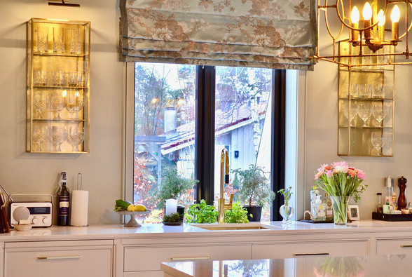 Vaskebenk med skuffer og oppvaskmaskin. Artige vegghengte glasshyller i messing