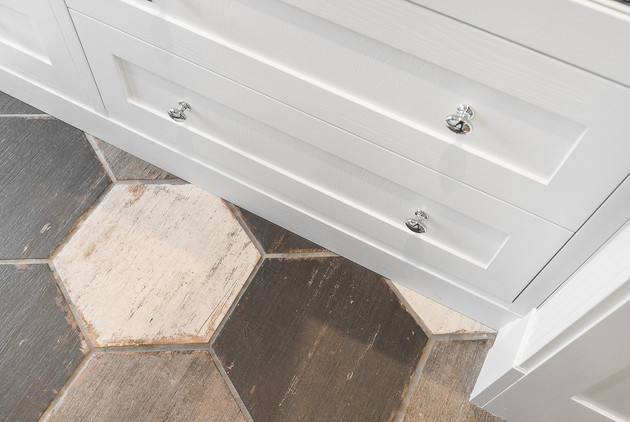 Detalj på garderoben av skuffefronter og sokkel i malt eikefinér og knotter i krom