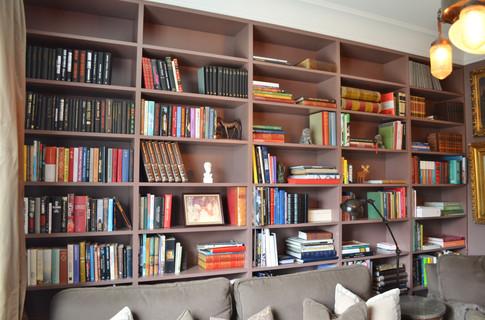 Bokhyller bak sofaen i burgunder farge