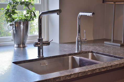 Kjøkkenbatteri med filtrert og nedkjølt vann med kullsyre, samt underlimt vask i stål. Benkeplate med ekstra dybde trukket helt ut mot vinduet