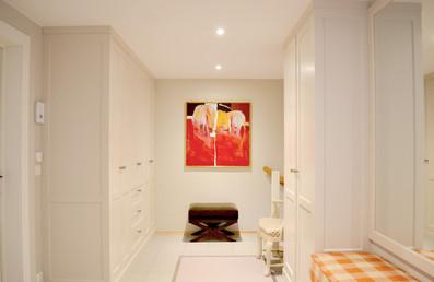 Skreddersydd garderobe til tak med åpningsdører i entre. Speil med ramme over sittebenk med håndsydd pute i rutemønster. Malt i lys grå farge_