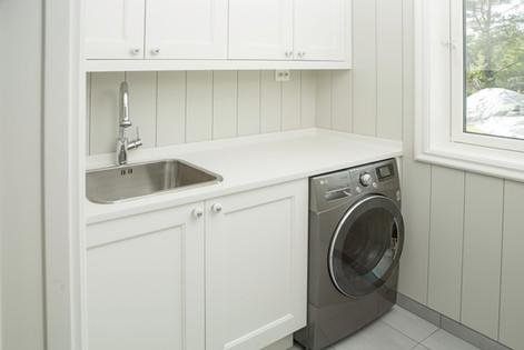 Innredning spesialtilpasset mindre vaskerom. Lys farge på skap og benkeplate med plass til vaskemaskin under benken. Armatur med dusj og dyp kum fra Intra