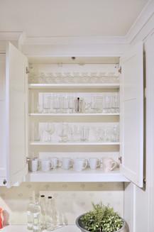 En liten titt inne i dette overskapet avslører det klassiske malte hyllene til her vist med drikkeglass og kaffekopper