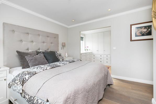 Spesilatilpasset seng med stofftrukket sengegavl og nattbord