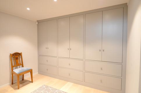 Stilren garderobe i mellomgang i Slett Inframe utførelse og eikefinert overflate