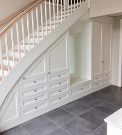 Garderobe med sittebenk og speil i klassisk stil bygget inn i trapperom