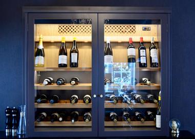 Tøft håndlaget vinskap på benk med glassdører i mørk blå farge som innredningen.