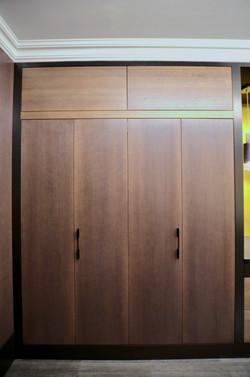 Et elegant og ryddig oppsett av høyskap som hinter om skjulte kjøkken skatter bak de flotte foldedørene i lakert eik med mørk beiset farge
