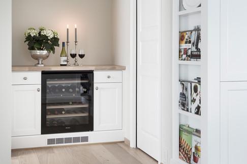 Egen avdeling av kjøkkenet til innredning i lys farge med integrert vinskap fra Miele og magasinholder
