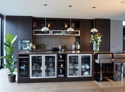 Spennende kjøkkeninnredning med slette fronter i mørk brun eik. Spesiallagede glassdører med ramme i aluminium på kjøkken øy og lave skap over benk. Kjøkkenet er tegnet i samarbeid med interiørdesigner VillaKildal