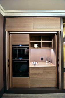 Bak foldedørene i høyskapsrekken skjuler det seg sorte elegante hvitevarer fra Siemens med praktisk avlastningsbord og med åpne hyller over