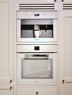 Innfelt kaffemaskin og stekeovn fra Miele i hvit skaper et sømløst preg mot den lyse kjøkkeninnredningen