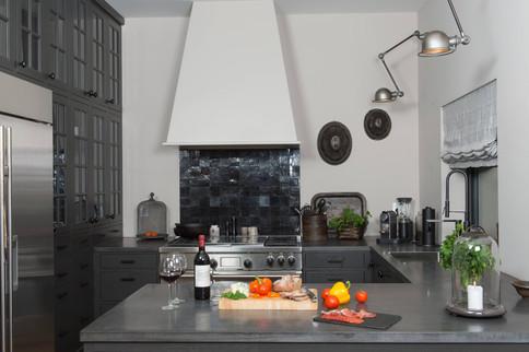 Kjøkkeninnredning med hel vegg til høyskaper og klassiske glassdører kombinert med innfelte slette fronter gir et massivt uttrykk med en åpen romfølelse