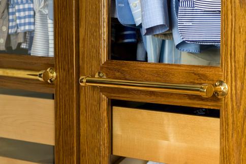 Detaljer fra walk in garderobe i mørkbeiset eik med glassdører og håndtak i messing
