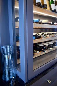 Glass i sidene på skapet er en detalj som er med på å  gjøre vinskapet til et naturlig midtpunkt på kjøkkenet