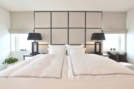 Polstret sengegavl til tak med håndsydde kvadrater og matchende lift gardiner fra Sirocco Design