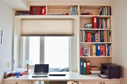 Skreddersydd bokhylle på gjesterom eller hjemmekontor tilpasset tak, vegger og vindu. Skrivepult med skap og skuffer. Malt i lys grå farge