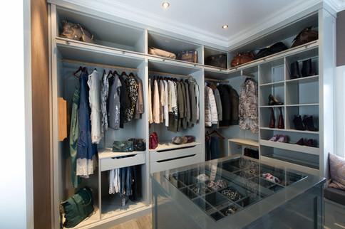 Plasstilpasset walk in closet med åpne garderobeskap og øy med et bredt utvalg praktiske løsninger