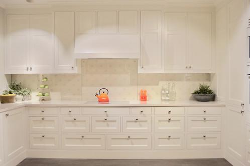Skuffer bygget opp som en kjøpmannsdisk gir et tøft uttrykk på dette kjøkkenet. Hvit kompositt benkeplate og antikk tinn knotter