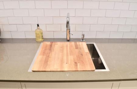 Vask med tilhørende skjærefjøl planlimt mot benkeplaten i kompositt stein. Armatur med kokende vann fra quooker og nedfelt såpedispenser