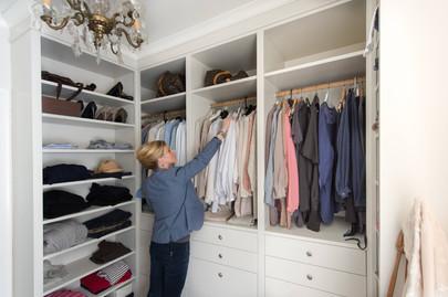 Spesialtilpasset walk in closet med et variert utvalg av garderobe heng, skuffer til undertøy og hyller til klær, sko, vesker og tilbehør