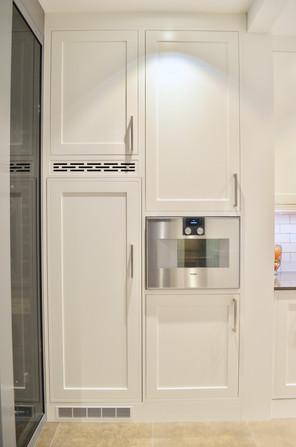 Høyskaps seksjon med innebygget kompakt kombi ovn og kjøleskap gir et sømløst preg