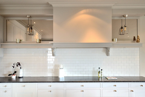 Kraftig kjøkkenhette med gjennomgående horisontal dekorhylle og bronsjespeil. Matchende hengelamper i stål. Benkeplate i camrian black granitt. Induksjonstopp fra V-zug