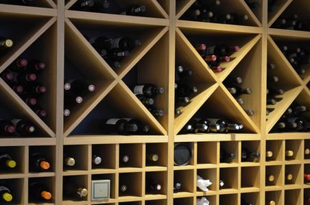 Krysshyllene i eik sammen med de små avlukkene til vinflaskene skaper variasjon og dybde i dette mesterverket av en vinhylle