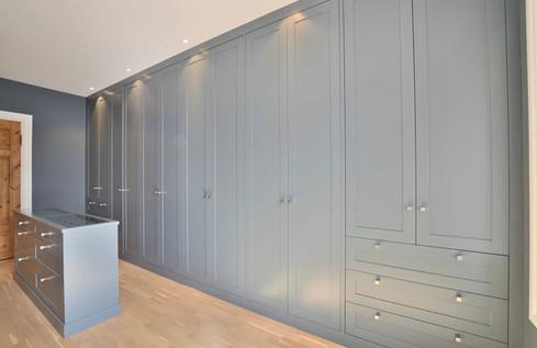 Garderobe mot vegg med skråtak skjult bak skapene. Vegg og innredning i farge St Pauls Blue. ONE kube knotter