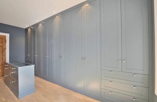 Garderobe mot vegg i St Pauls Blue med skråtak skjult bak skapene. Smal garderobe øy med fire dype skuffer og to toppskuffer
