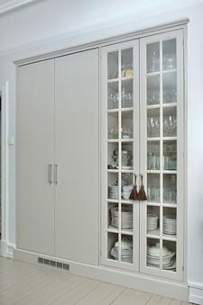 Innebygget seksjon med stort dobbelt kjøleskap og vitrineskap med glassdører på dette kjøkkenet i landsted stil