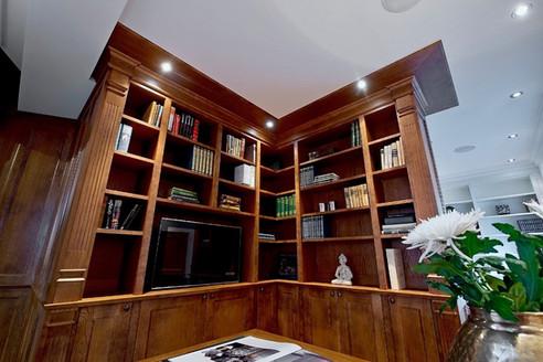 Bokhyller med utsmykkede pilastere og nedsenkbar TV