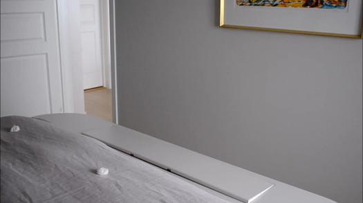 Garderobe og seng med innebygget TV i lys grå og dusty lilla